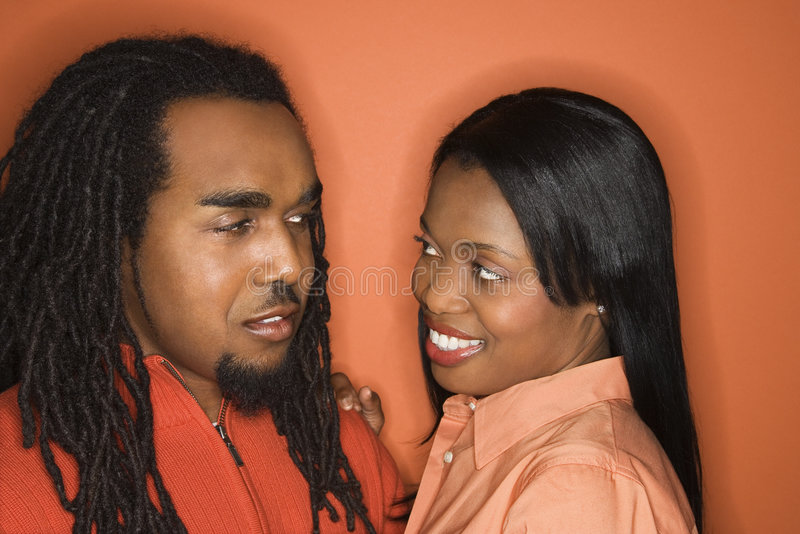 orange slitage för afrikansk amerikanklädpar arkivfoton