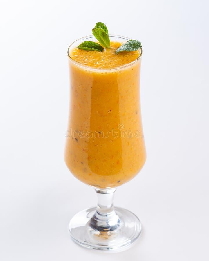 Orange smoothie i ett högväxt exponeringsglas som dekoreras med ett blad av mintkaramellen på vit bakgrund arkivfoton