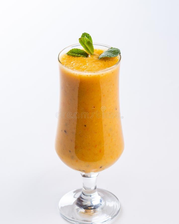 Orange smoothie i ett h?gv?xt exponeringsglas som dekoreras med ett blad av mintkaramellen p? vit bakgrund arkivfoton