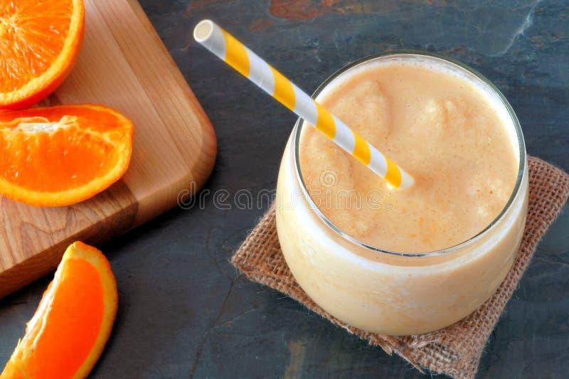 Orange Smoothie mit Scheiben des gestreiften Strohs und der frischen Frucht stockbild