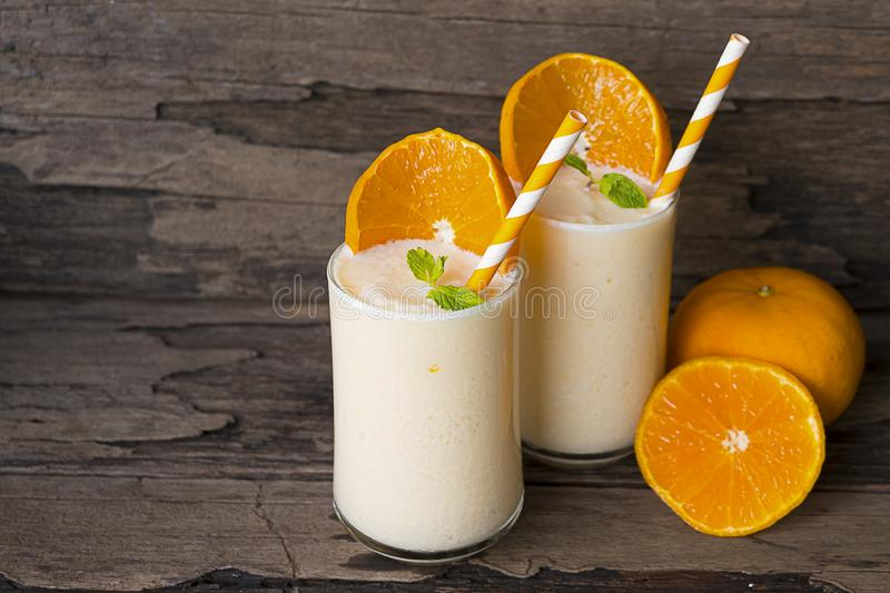 Orange smoothies fruit on old wood background. Orange smoothies orange colorful fruit juice beverage healthy high protein the taste yummy in glass on  wood royalty free stock photo