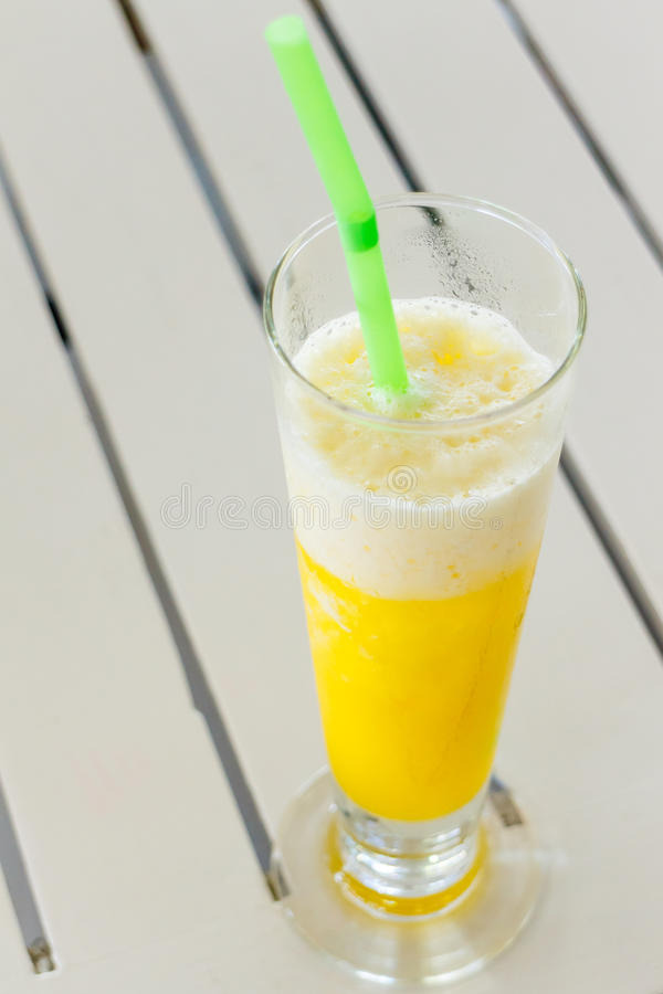 Orange smoothies. In glass and green tube on wood table stock images