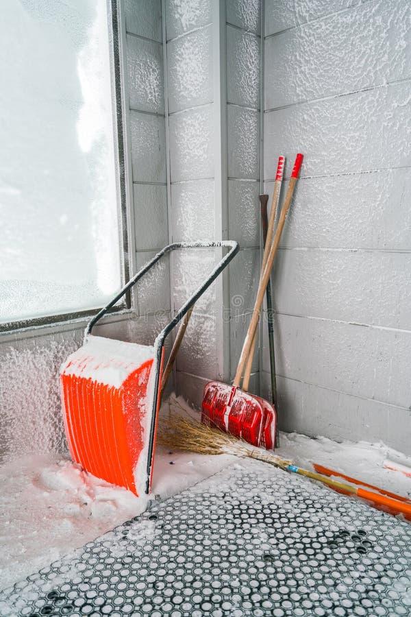 Orange snöborttagning Skyffel i snö royaltyfri foto