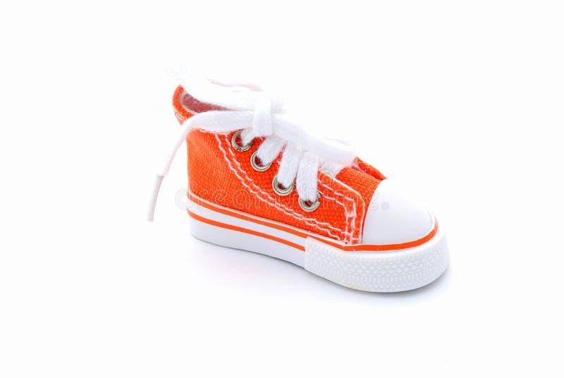 Orange sneaker. A single new orange baby sneaker shoe. Image isolated on white studio background stock photo