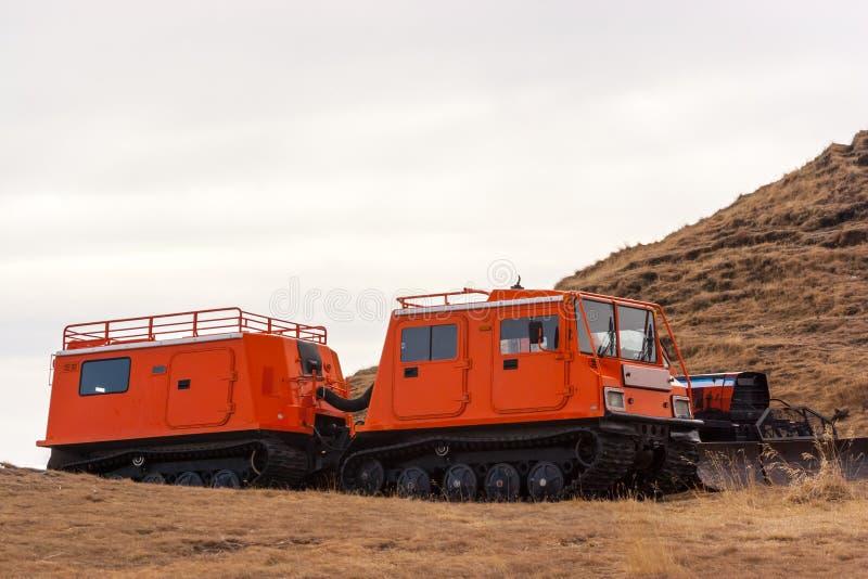 Orange snowcat med den andra vagnen Ett annat medel med snöplogen arkivbild