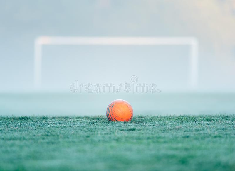 An orange soccer ball centered in front of an out of focus soccer goal stock photos