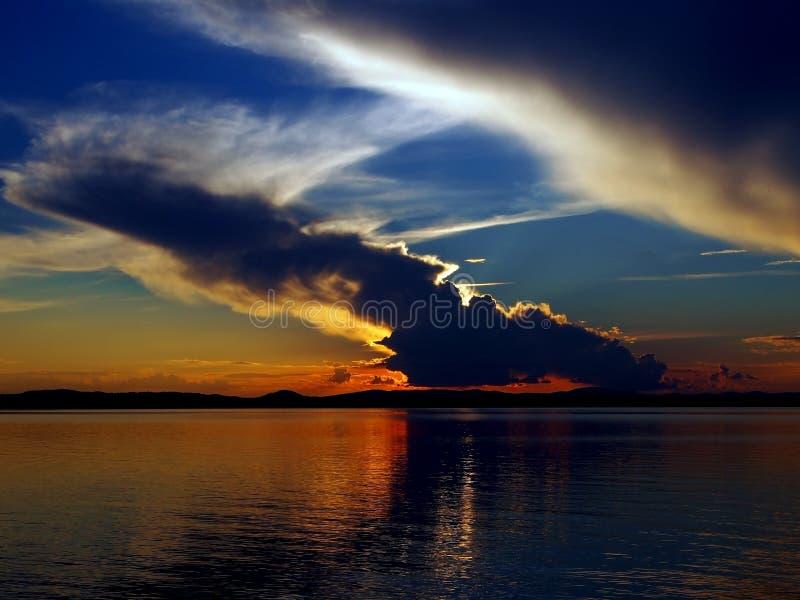 Orange sol på den blåa solnedgånghimlen med fjäderlika dramatiska moln över sjön, sydliga Urals arkivfoton