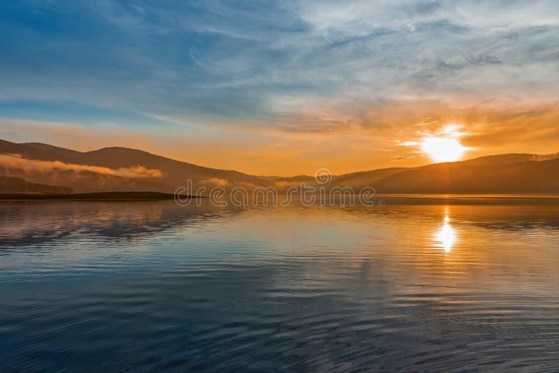 Orange solnedgång över bergsjön arkivfoton