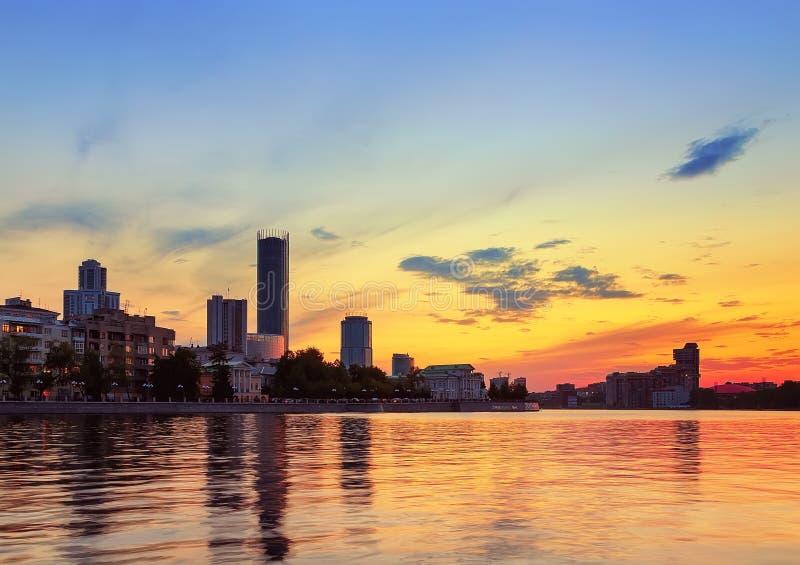 Orange solnedgång över stadsdammet i Yekaterinburg royaltyfria bilder