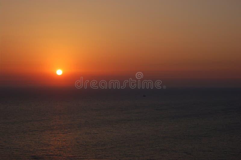 Orange solnedgång ovanför det lugna havet royaltyfria bilder