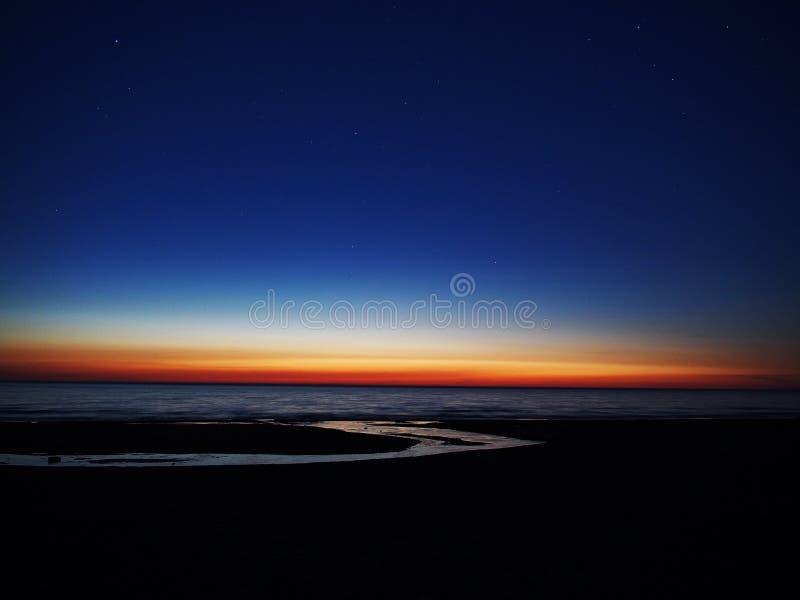 Orange Sonnenuntergang und Sterne über Meer stockfoto