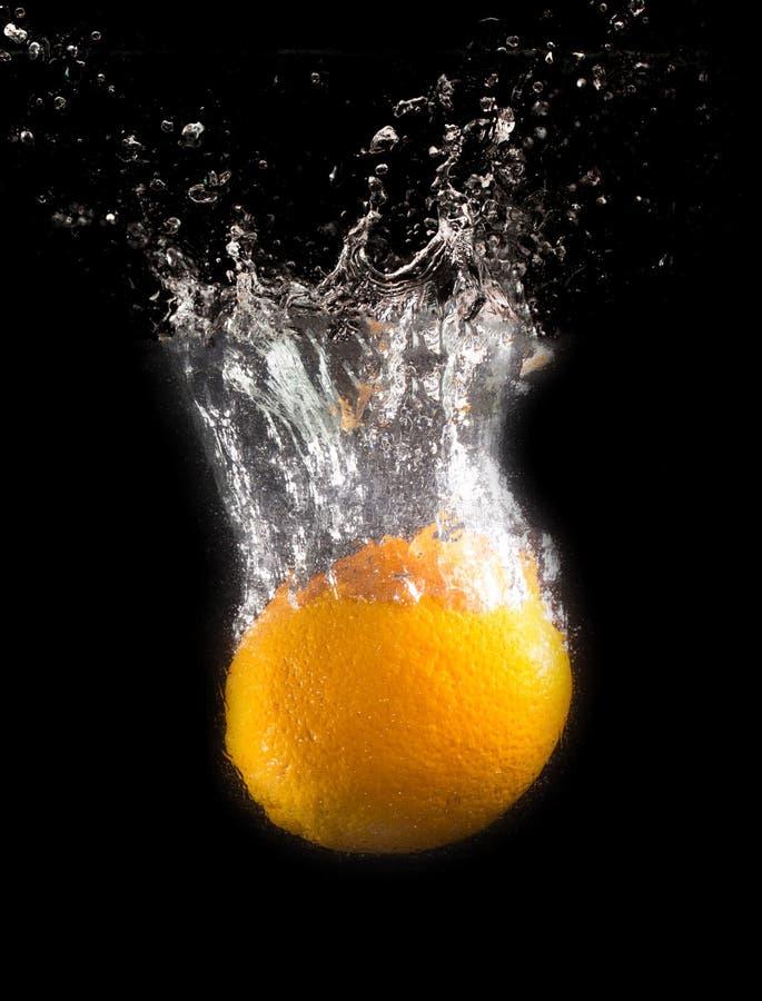 Orange sous l'eau sur un fond noir photographie stock