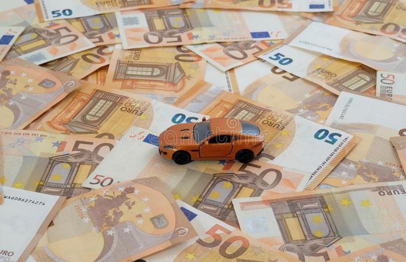 Orange sports car on bills concept car costs. A model car on laid out 50 Euro banknotes as concept car costs stock photo