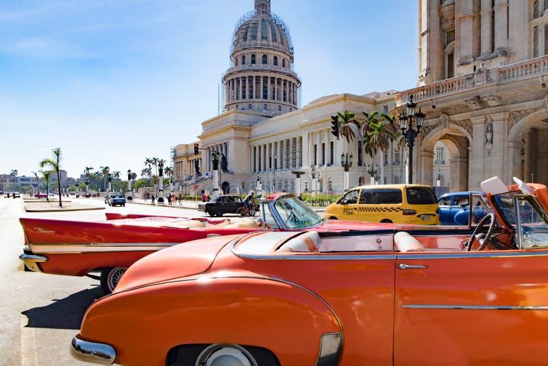 Orange stänkskärm av amerikanska klassiska bilar framme av Capitolio, havannacigarr, Kuba royaltyfri fotografi