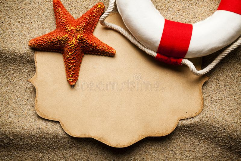 Orange starfish, red and white lifebuoy and blank paper label stock photo
