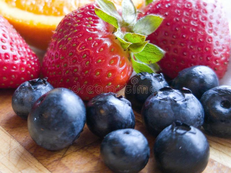 Orange Stawberry Blueberry Fruits on Wooden Cutting Board stock image