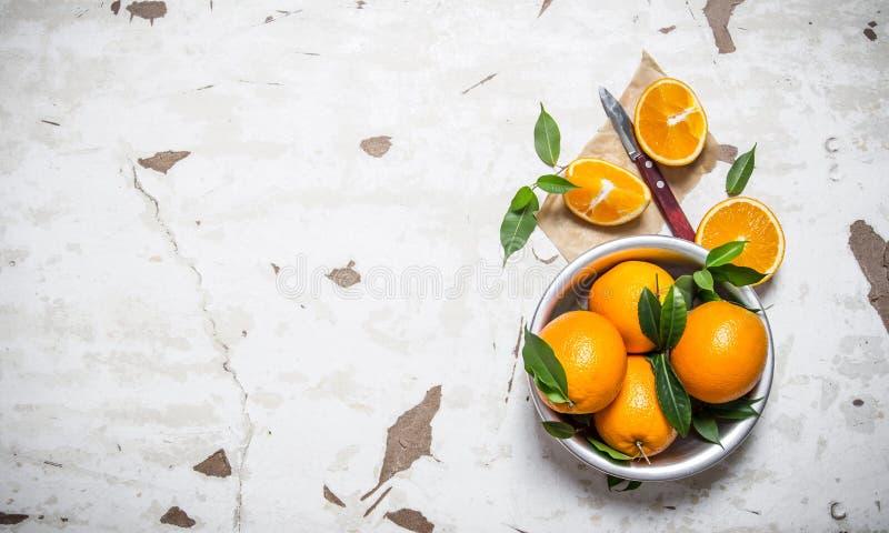 orange stil Nya apelsiner med sidor i en kopp royaltyfri bild