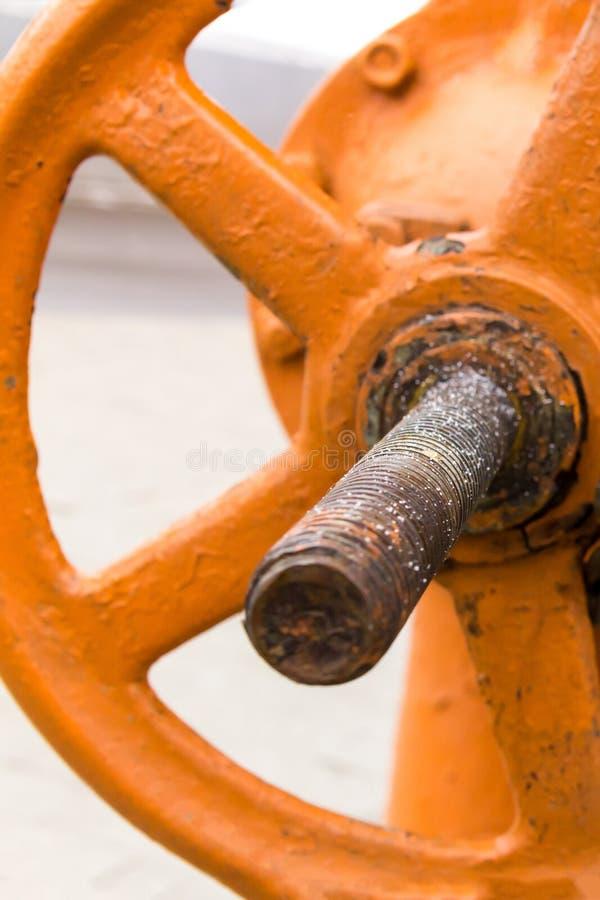 Orange stor ventildel av den industriella närbilden för gasledningsystem och för oljeproduktiondesign med en lång rostig grund royaltyfri bild