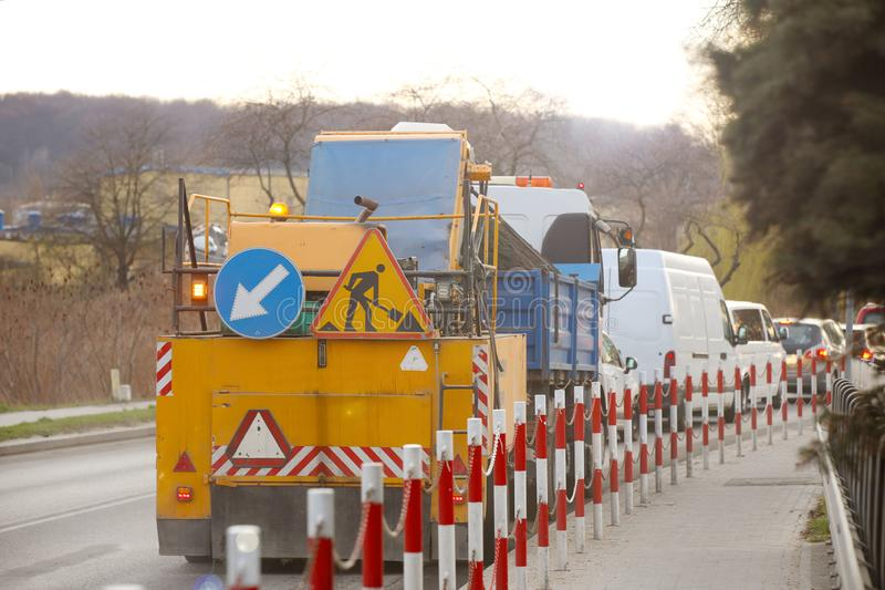 An orange street-cleaning machine stands in a traffic jam near the sidewalk designated by signal barriers. Road marking signs. During road works. Restriction of stock image