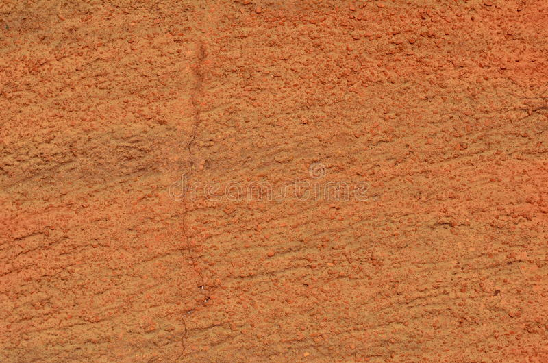 Orange stucco texture. Cracked wall with stucco coating airbrushed with orange graffiti paint royalty free stock images