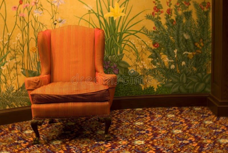 Orange Stuhl vor Blumenwand stockbild