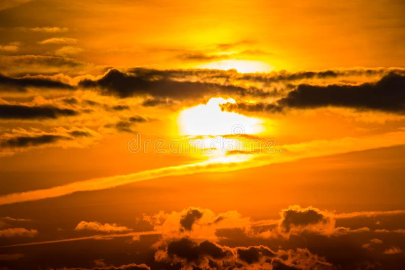 Orange sun in cloudy sky royalty free stock photos