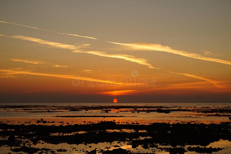 Orange Sun Goes Down. Beautiful sunset at Bawean, East Java, Indonesia. Perfect landscape at beach. Sun goes down the horizon stock images
