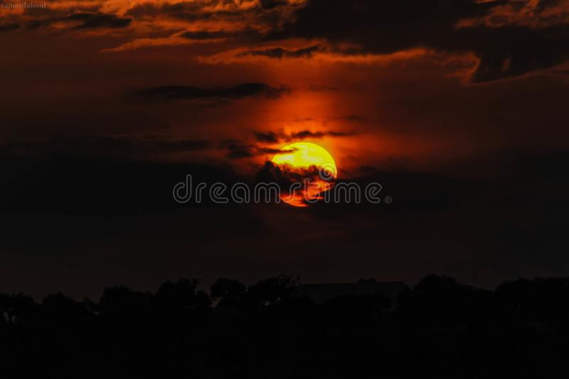 Orange Sun Hiding on Clouds stock photography