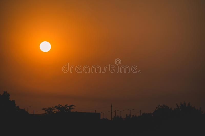 Orange sun at sunset on background of black silhouette of trees and houses. Orange sun at sunset on background of black silhouette of trees and houses royalty free stock photos