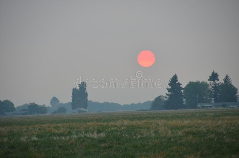 Orange sun at sunset in Oregon`s Willamette Valley. This is a sun setting in Oregon`s Willamette Valley in a haze caused by forest fires stock photo