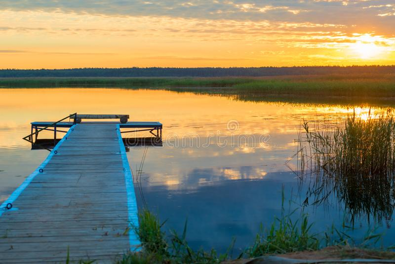 Orange sun at sunset over a picturesque lake with a beautiful wooden pier royalty free stock photo