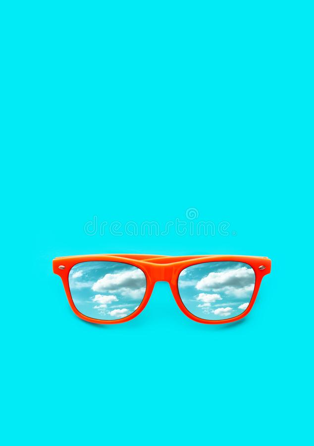 Orange sunglasses with blue sky with clouds reflections isolated in vertical cyan blue background. Summer concept. stock images