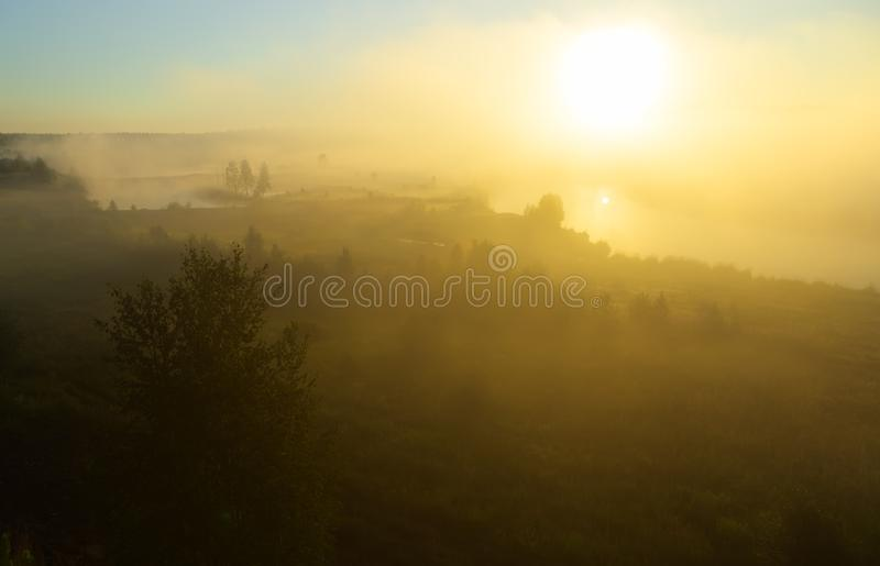 Orange sunny light with rays and shadows over the foggy river at dawn. The fog rises above water and stretches to the royalty free stock photography