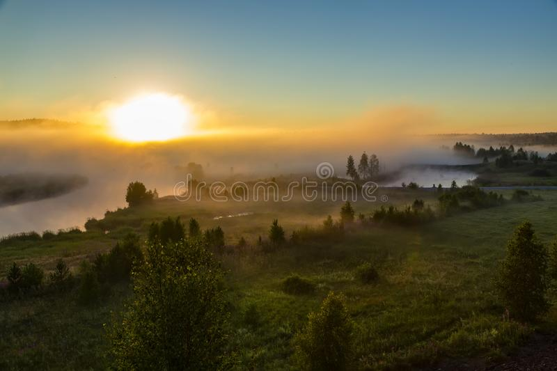 Orange sunny light with rays and shadows over the foggy river at dawn. The fog rises above water and stretches to the. Orange sunny light with rays and shadows stock photography