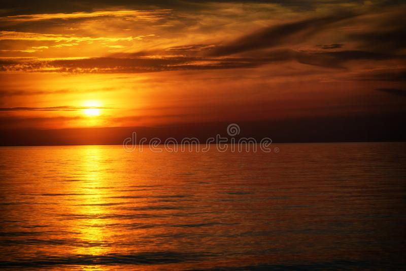 Dark cloudy orange sunset at the end of the summer. Beautiful dark cloudy orange sunset at the end of the summer by the ocean royalty free stock images