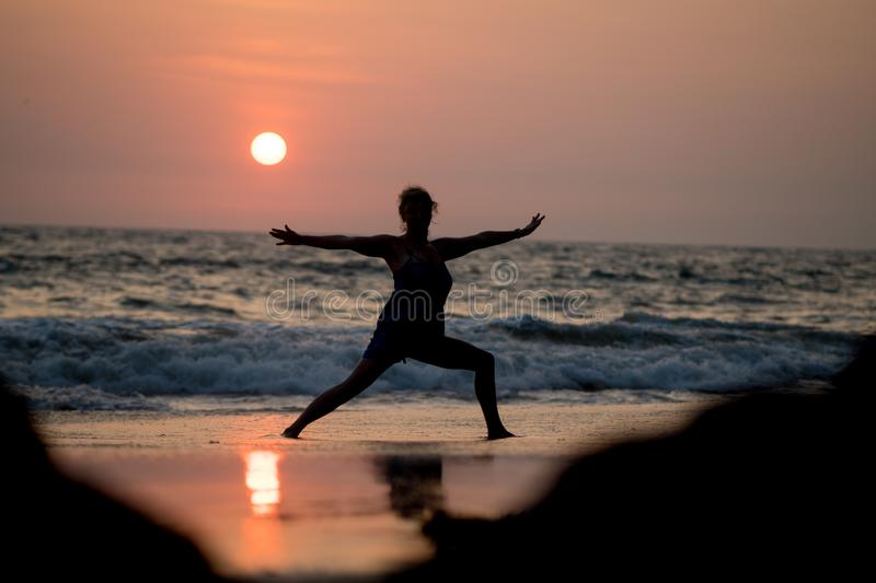 Yoga silhouette at ocean cost and sunset India royalty free stock images