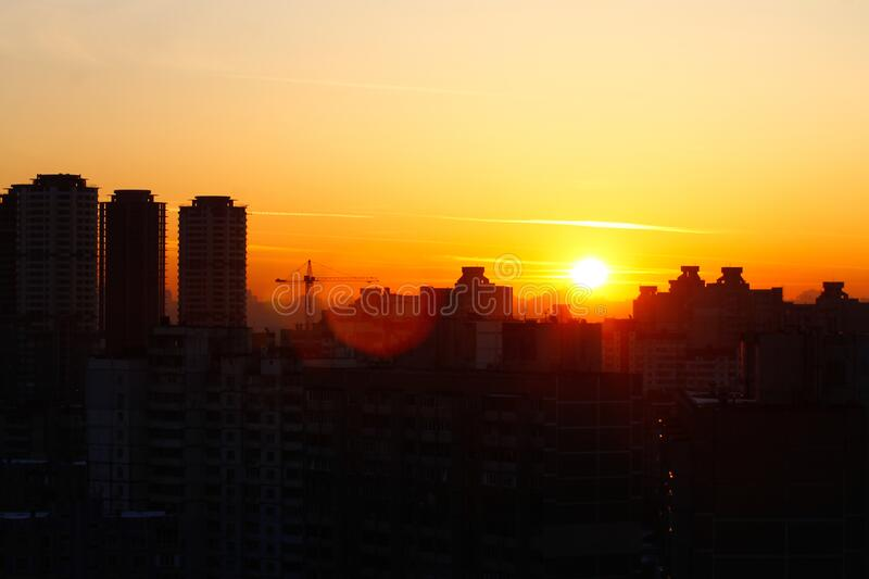 Orange sunset on the background of the city. Silhouette of a construction crane. Photo with a glare from the sun. Panorama of the stock photography