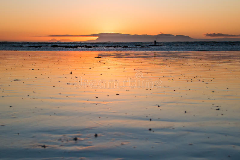 Orange Sunset. Beach sunset with orange colors and fisherman royalty free stock images