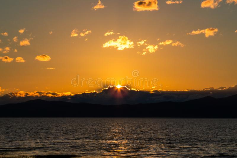 Orange Sunset Behind the Clouds/Mountains. And a big riverSaint-Lawrence River. Countryside, The Province of Quebec, Canada royalty free stock photos