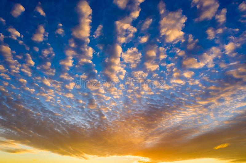 Orange sunset with clouds and blue sky above stock photo