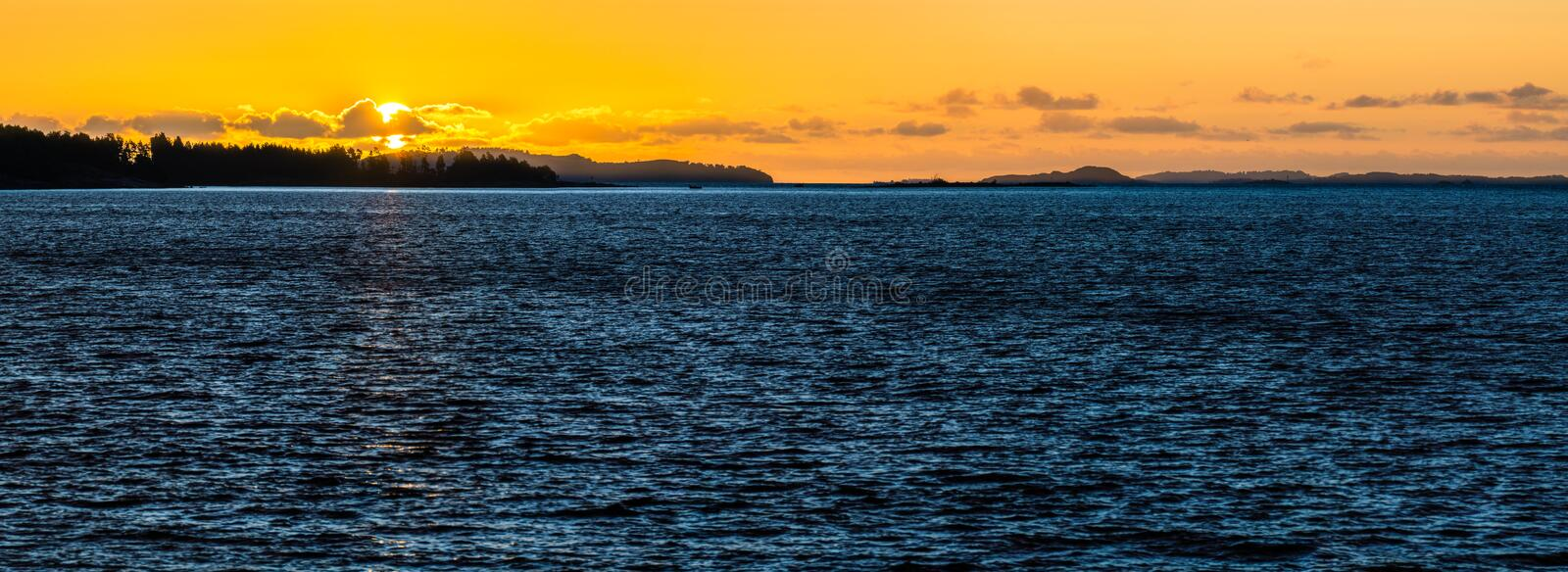 Orange sunset with deep blue water in Scandinavia. Midnight sun with reflections. stock photos