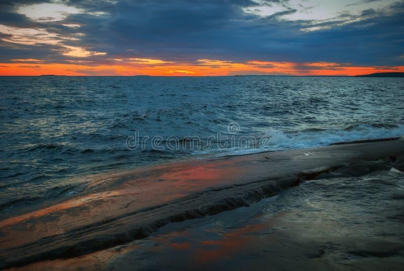 Orange Sunset Over a Stormy Lake royalty free stock photos
