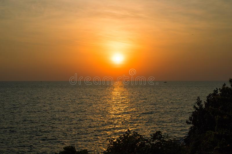 Orange sunset landscape with sea and trees. Vivid orange sunset sky. Romantic evening seascape with sunset. royalty free stock photo