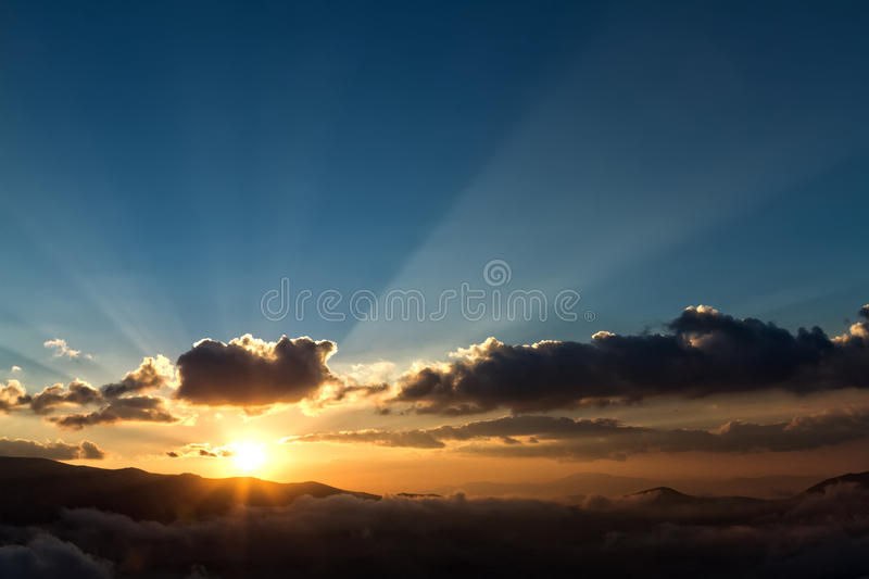 Sunset in mountains with sunbeams stock photo