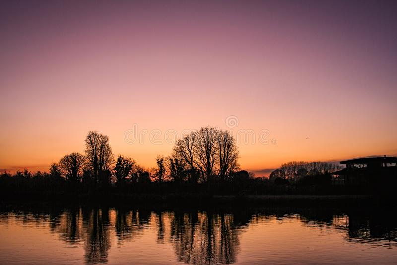 Orange sunset near Kingston upon Thames in England in December. Trees in silhouette reflected in the River Thames. A vignetted clear winter sky royalty free stock photo