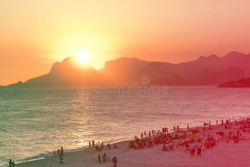 Orange sunset by the ocean in Piratininga, Niteri, with sun dipping behing the Gavea Stone in Rio de Janeiro. A beach full of peop. Le can be seen in the stock images