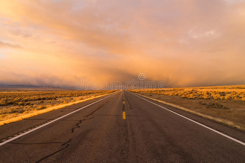 Orange Sunset Open Road Two Lane Highway Horizontal. A side road off the interstate stormy skies at sunset royalty free stock photo