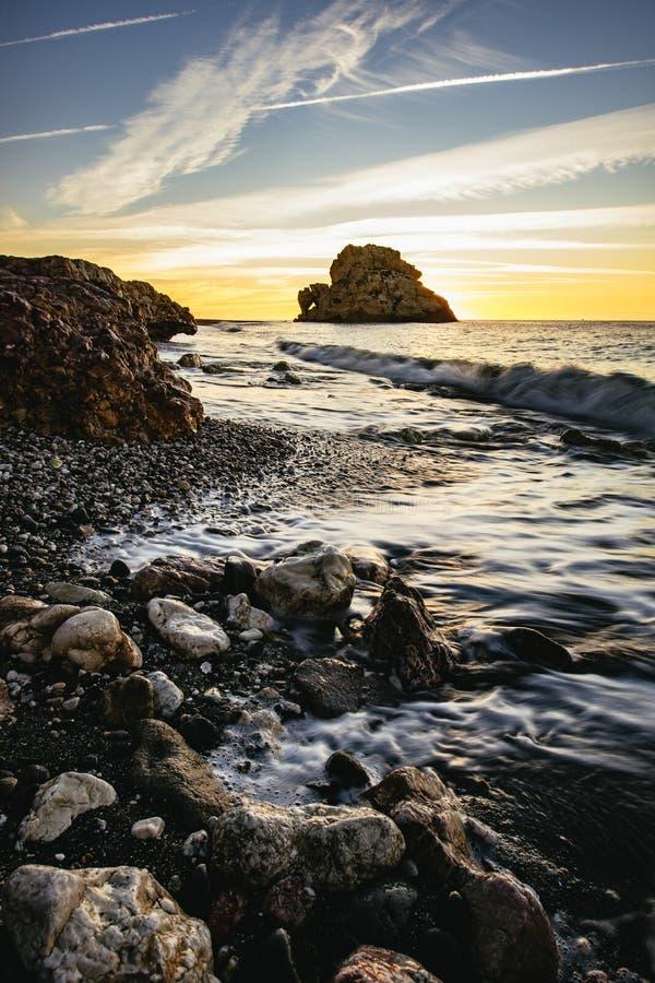 Orange sunset over a rocky coastline, Malaga Beach stock photo