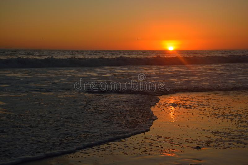 Orange sunset over the waves at Santa monica beach stock images