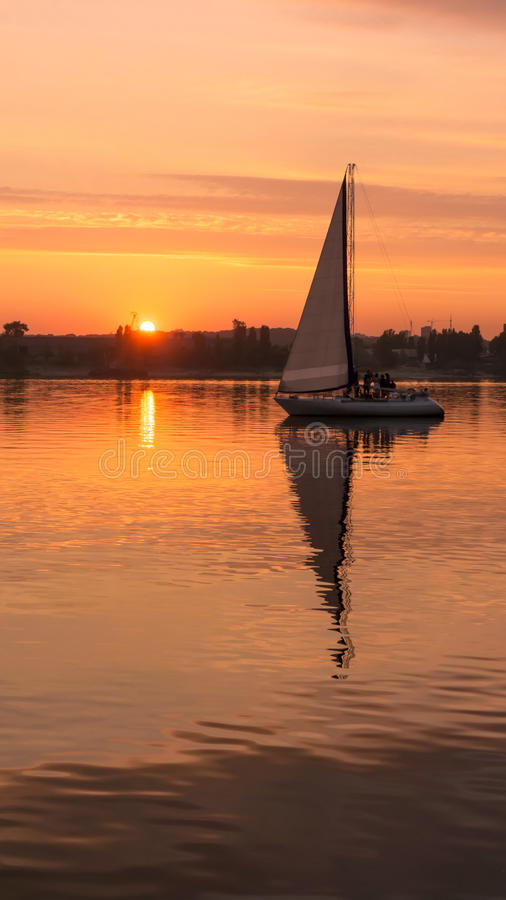 Orange sunset with a sail vertical landcsape stock photography
